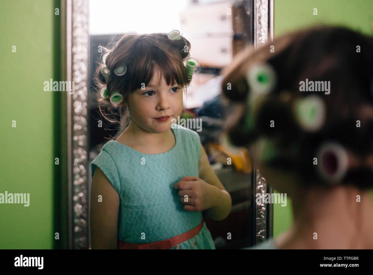 Chica con rizadores de pelo reflejando en el espejo estando en casa Imagen De Stock