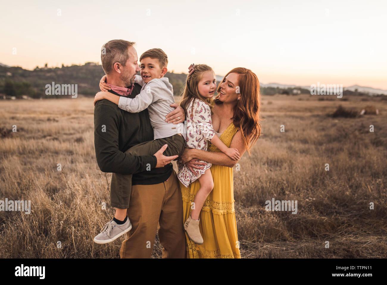 Chico y chica celebrado por sus padres en el campo de California durante la puesta de sol Foto de stock