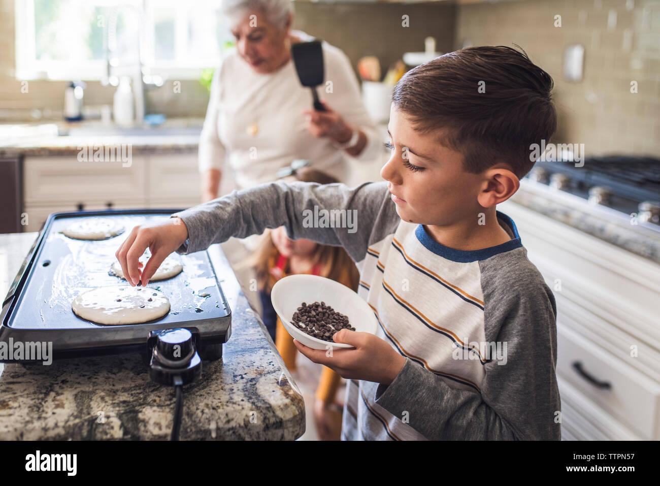 Joven cocina tortitas con familia multigeneracionales Foto de stock