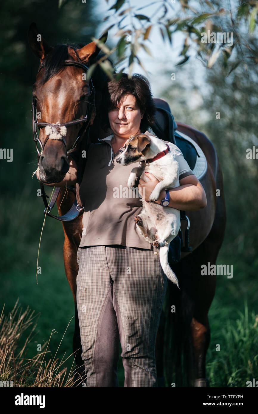 Retrato de mujer que llevaba cachorro mientras está de pie con el caballo en el campo Foto de stock