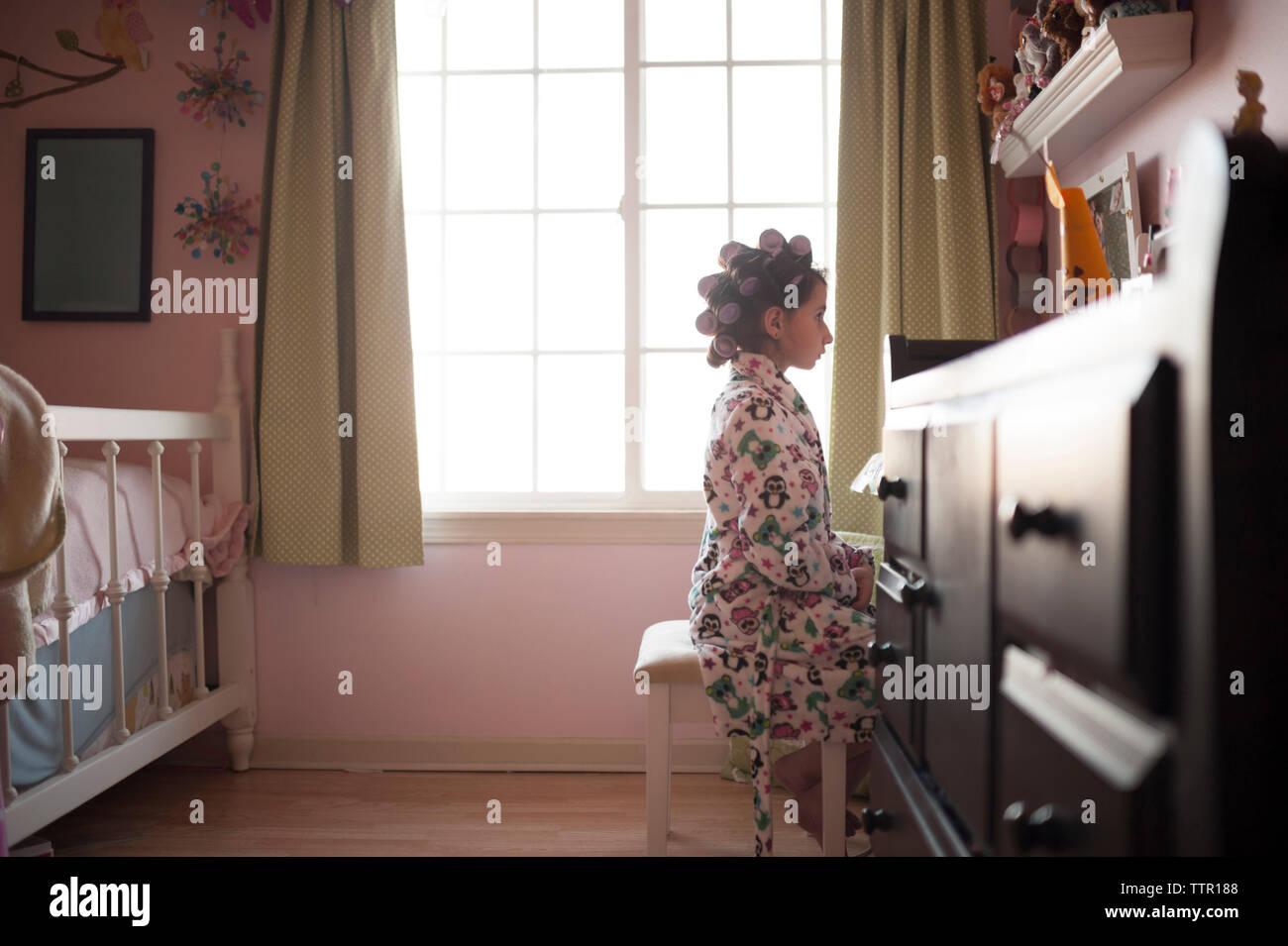 Vista lateral de la niña con rizadores de pelo sentado en heces en dormitorio Imagen De Stock