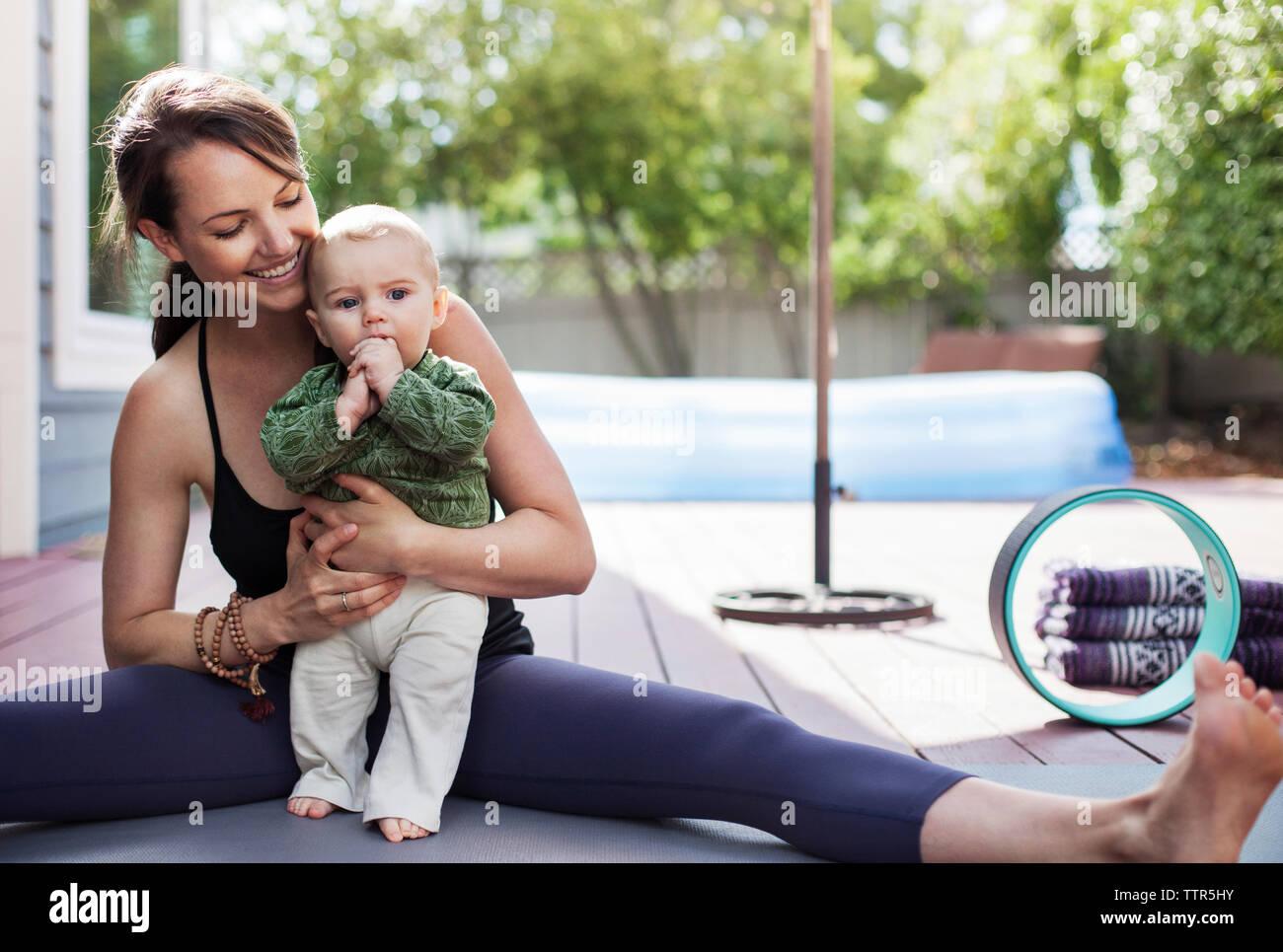 Madre sonriente sosteniendo bebé y mientras está sentado con las piernas Imagen De Stock