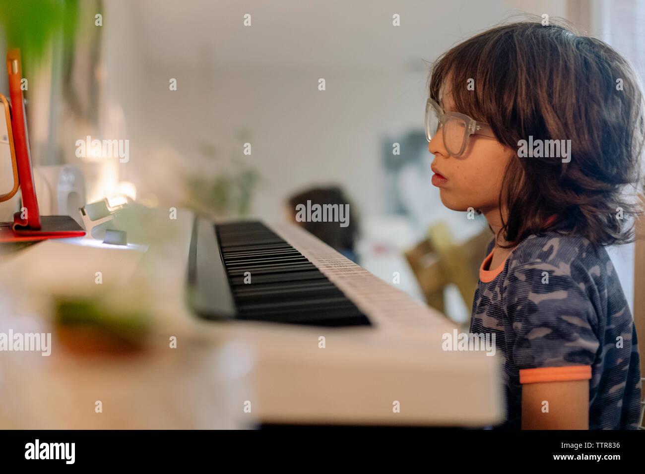 Vista lateral del niño con gafas mirando tableta smart piano keyword en casa Foto de stock
