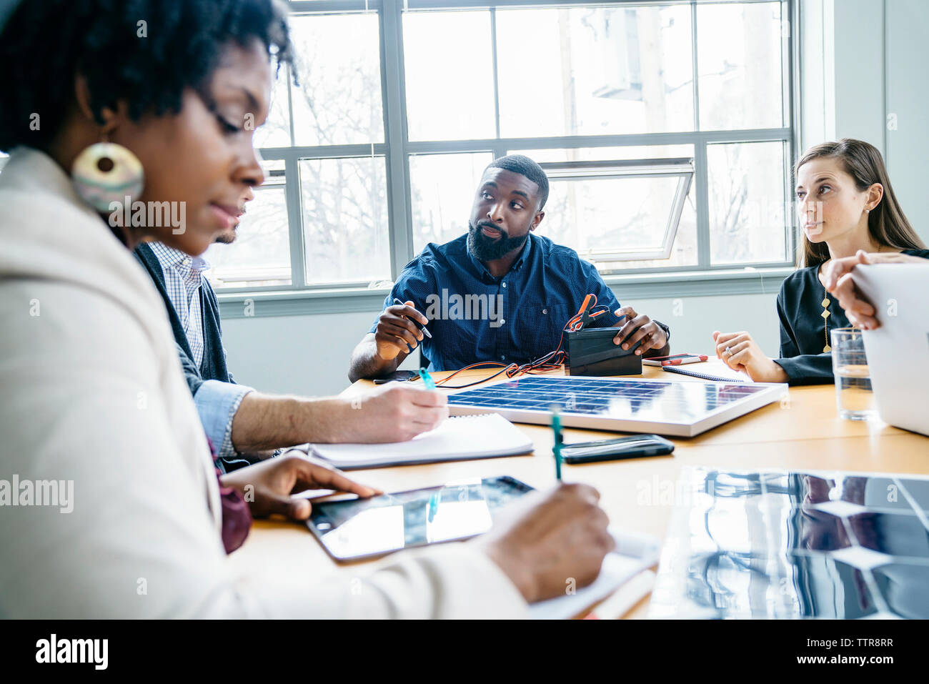 Gente de negocios discutiendo sobre el modelo de panel solar en Office Imagen De Stock