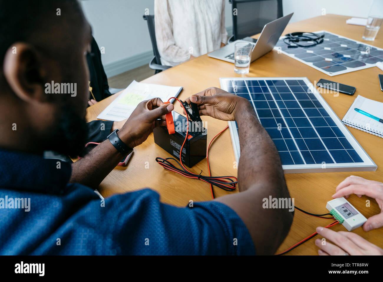 Cerca del empresario adjuntando clips metálicos sobre la batería mientras está trabajando en el modelo de panel solar Imagen De Stock