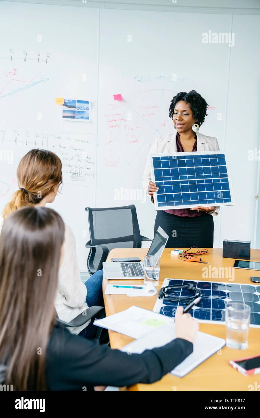La empresaria explicando el modelo de panel solar a sus colegas mujeres durante la reunión Imagen De Stock