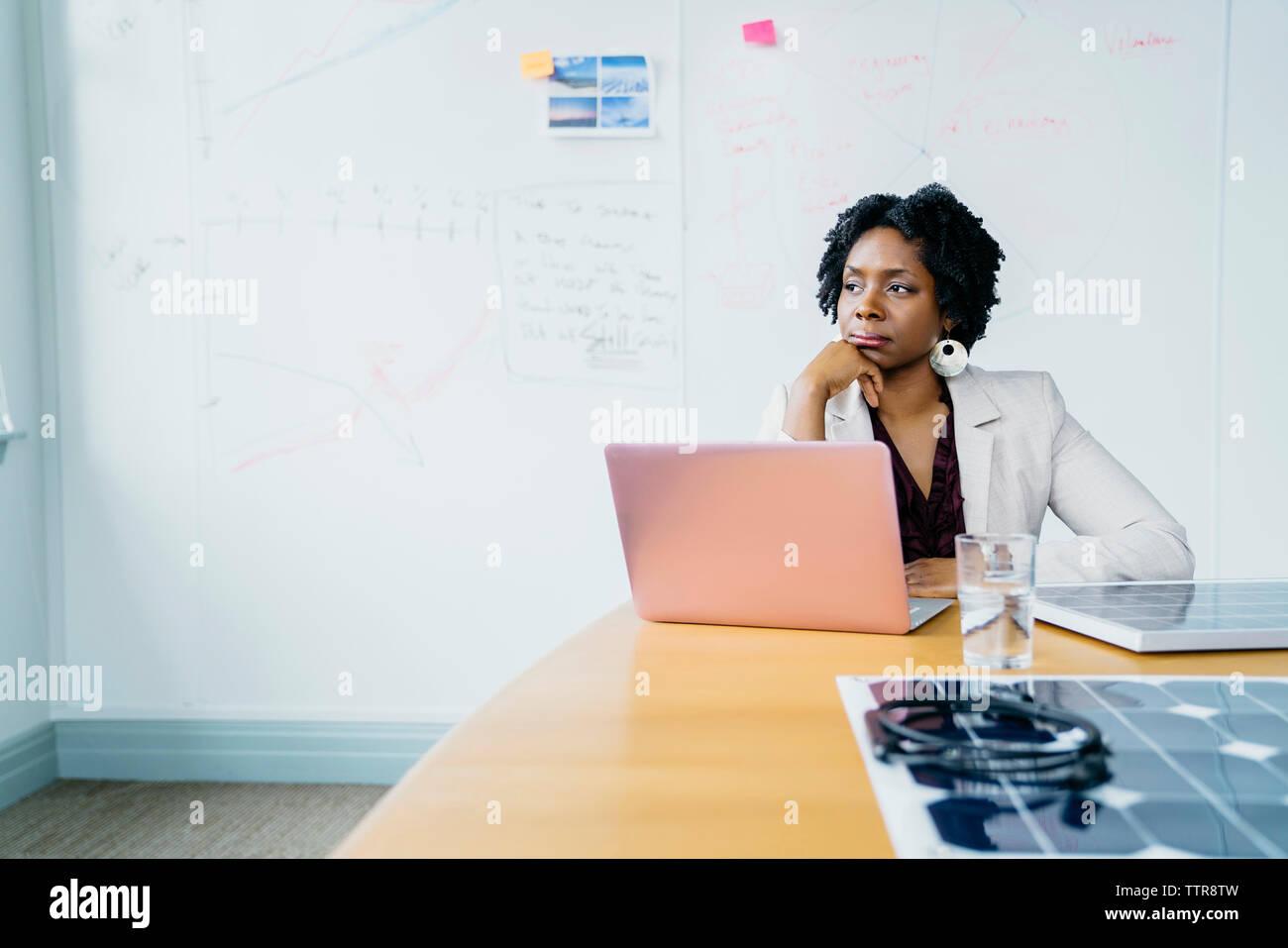 Pensativo empresaria con la mano en el mentón sentada contra la pizarra en Office Imagen De Stock