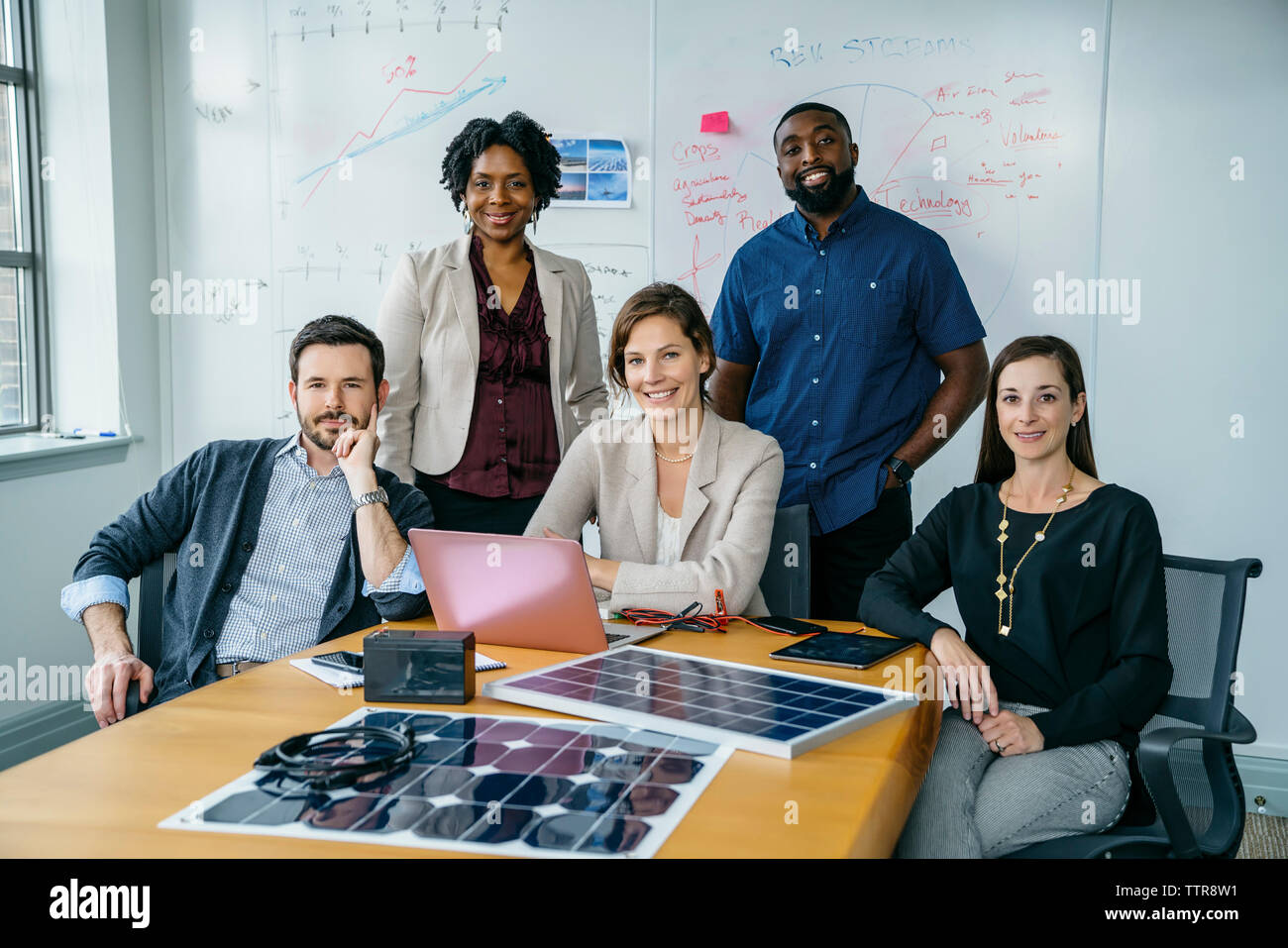 Retrato de gente de negocios sonriendo por modelos de paneles solares en la mesa. Imagen De Stock