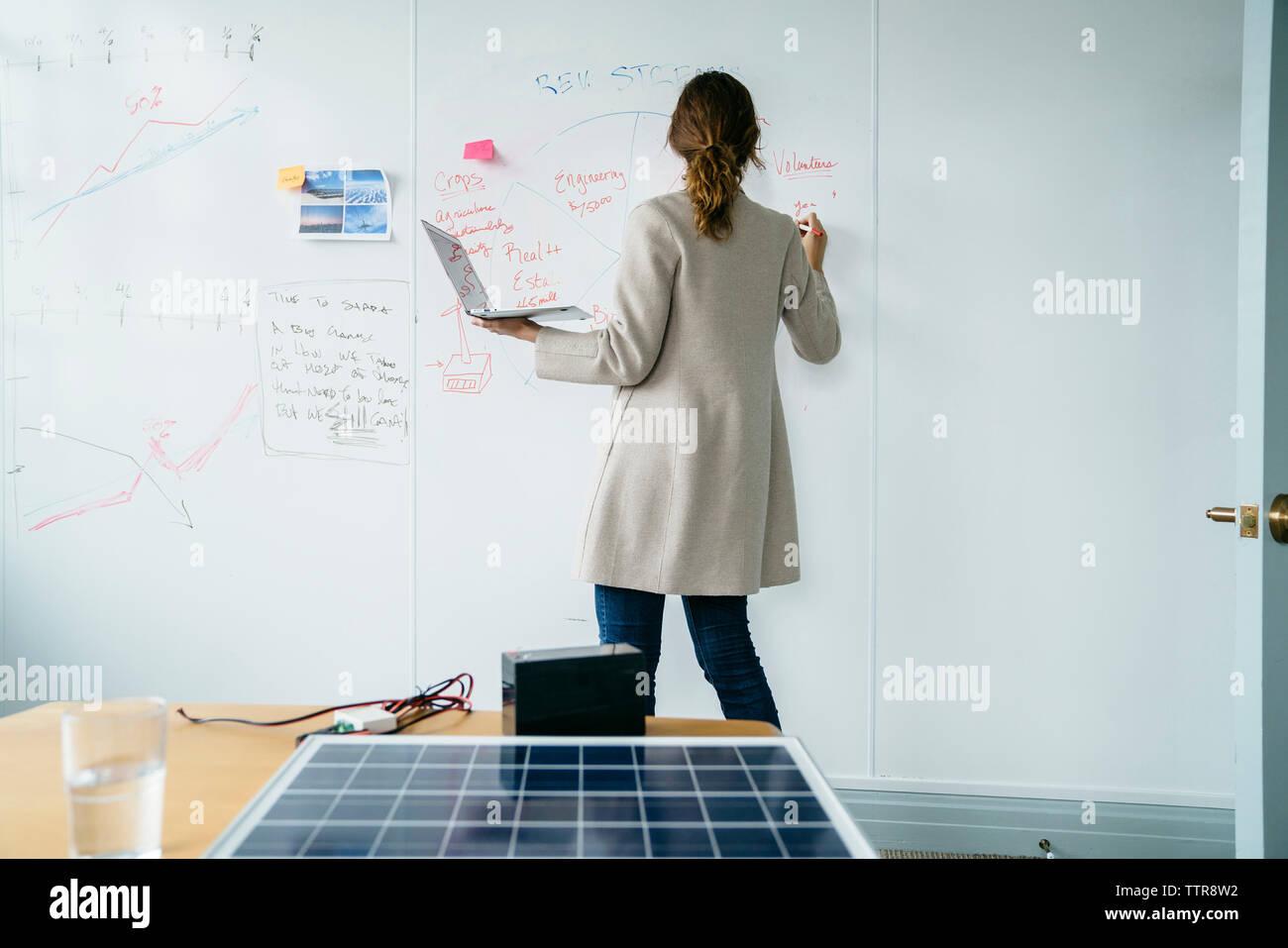 Vista trasera de la empresaria escrito en pizarra mientras trabaja a través de paneles solares en la oficina Imagen De Stock