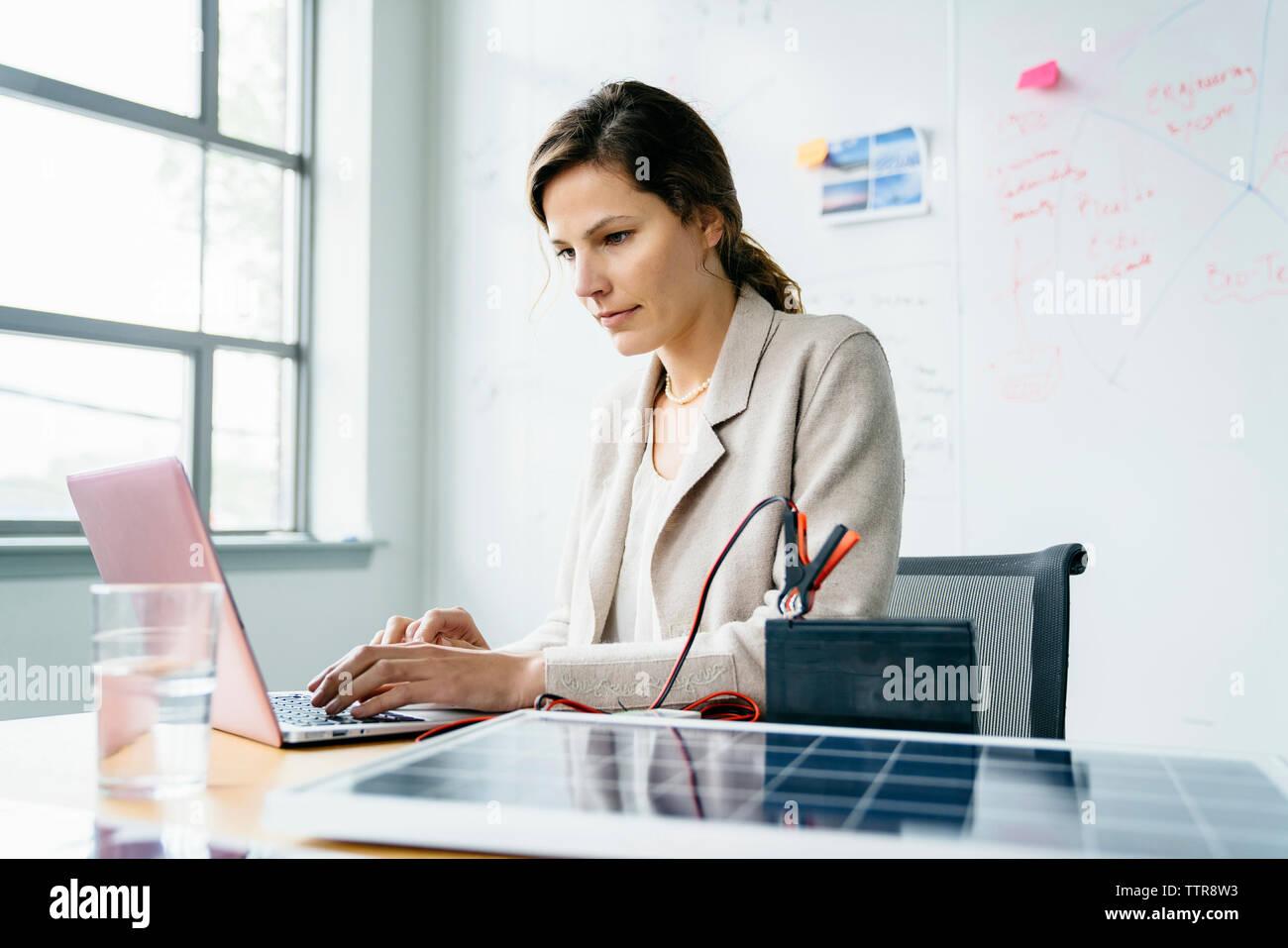 La empresaria mediante ordenador portátil mientras está sentado contra la pizarra en Office Imagen De Stock