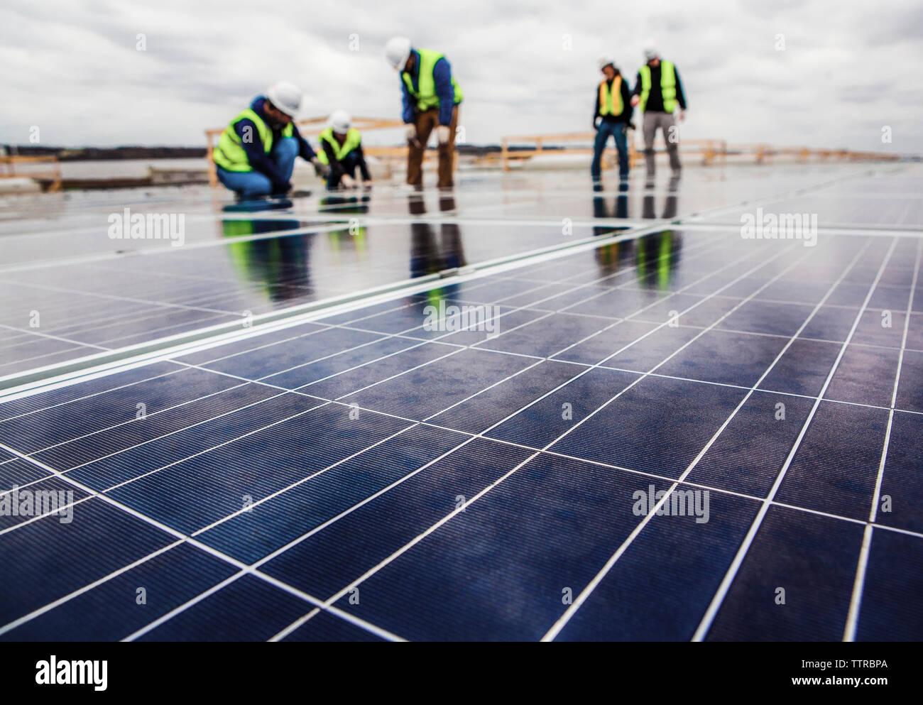 Los trabajadores que trabajan en el campo de panel solar contra el cielo nublado Imagen De Stock
