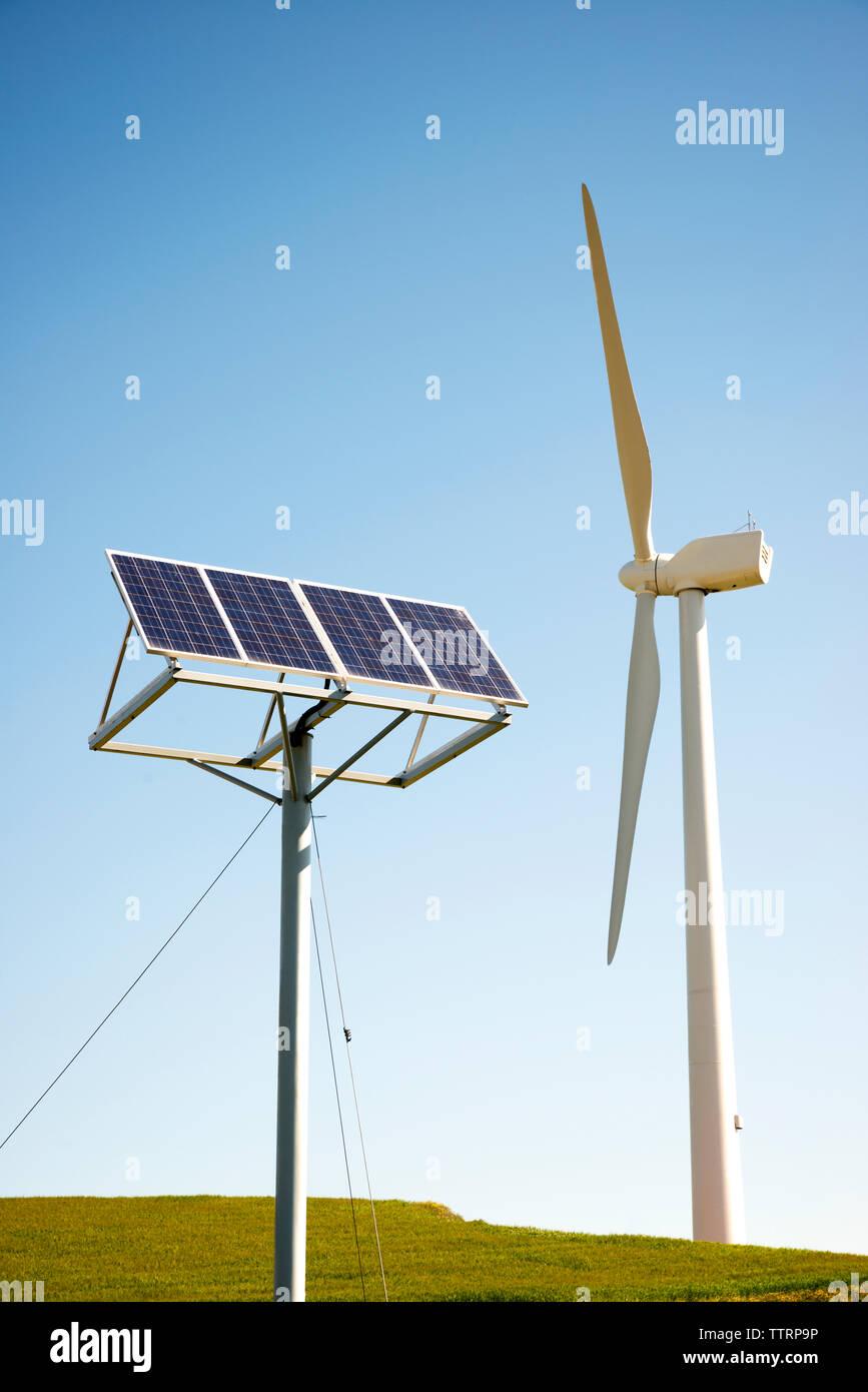 Turbinas de viento y paneles solares en campo contra el cielo claro Imagen De Stock
