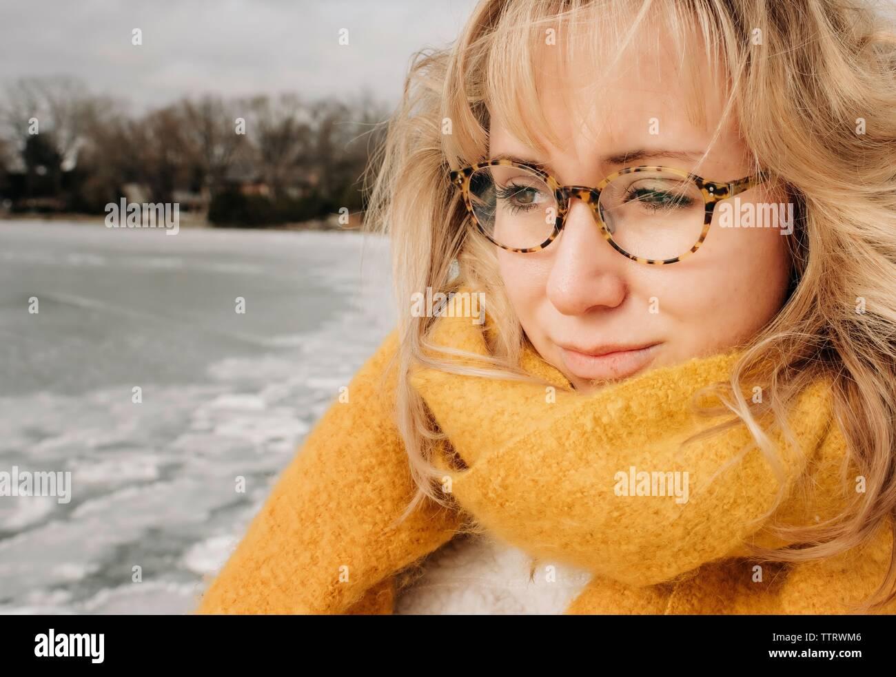 Retrato de mujer rubia con gafas mirando al agua sonriendo Foto de stock