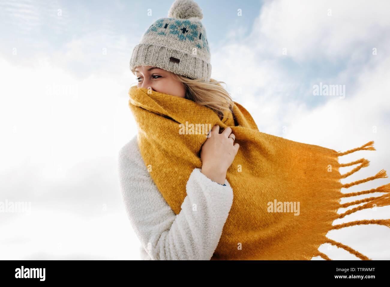 Mujer rubia riendo detrás de la bufanda en la playa en invierno Foto de stock
