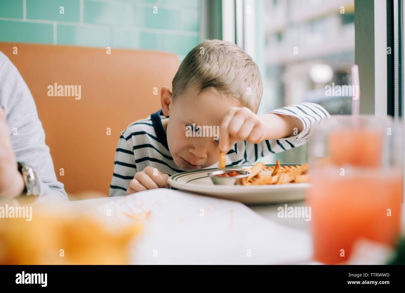 Joven comiendo papas fritas se sumerge en salsa en un restaurante Foto de stock