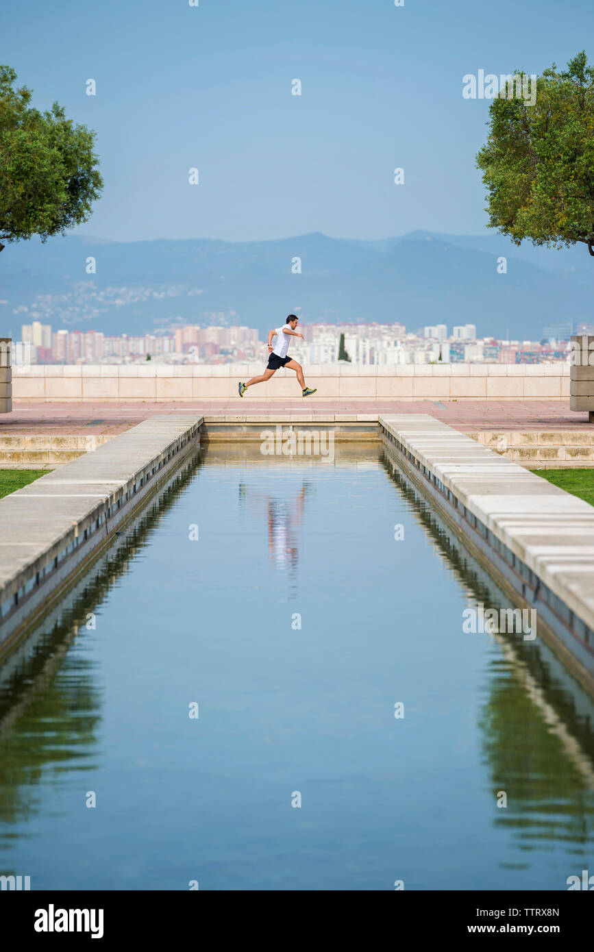 Vista lateral del hombre corriendo en muro de contención contra el cielo azul claro en park Foto de stock