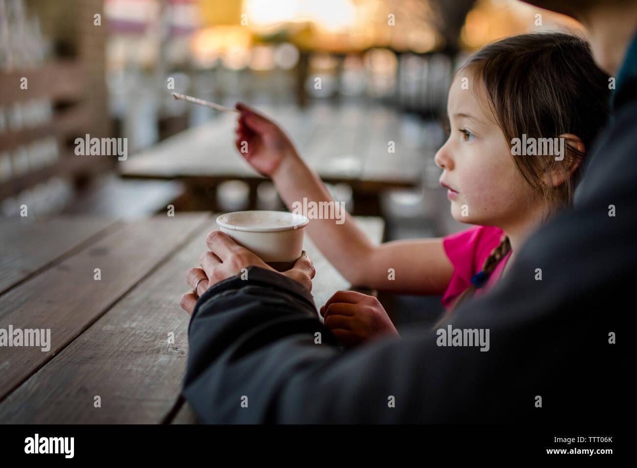 Un niño se sienta con su padre en un café al aire libre al atardecer Foto de stock