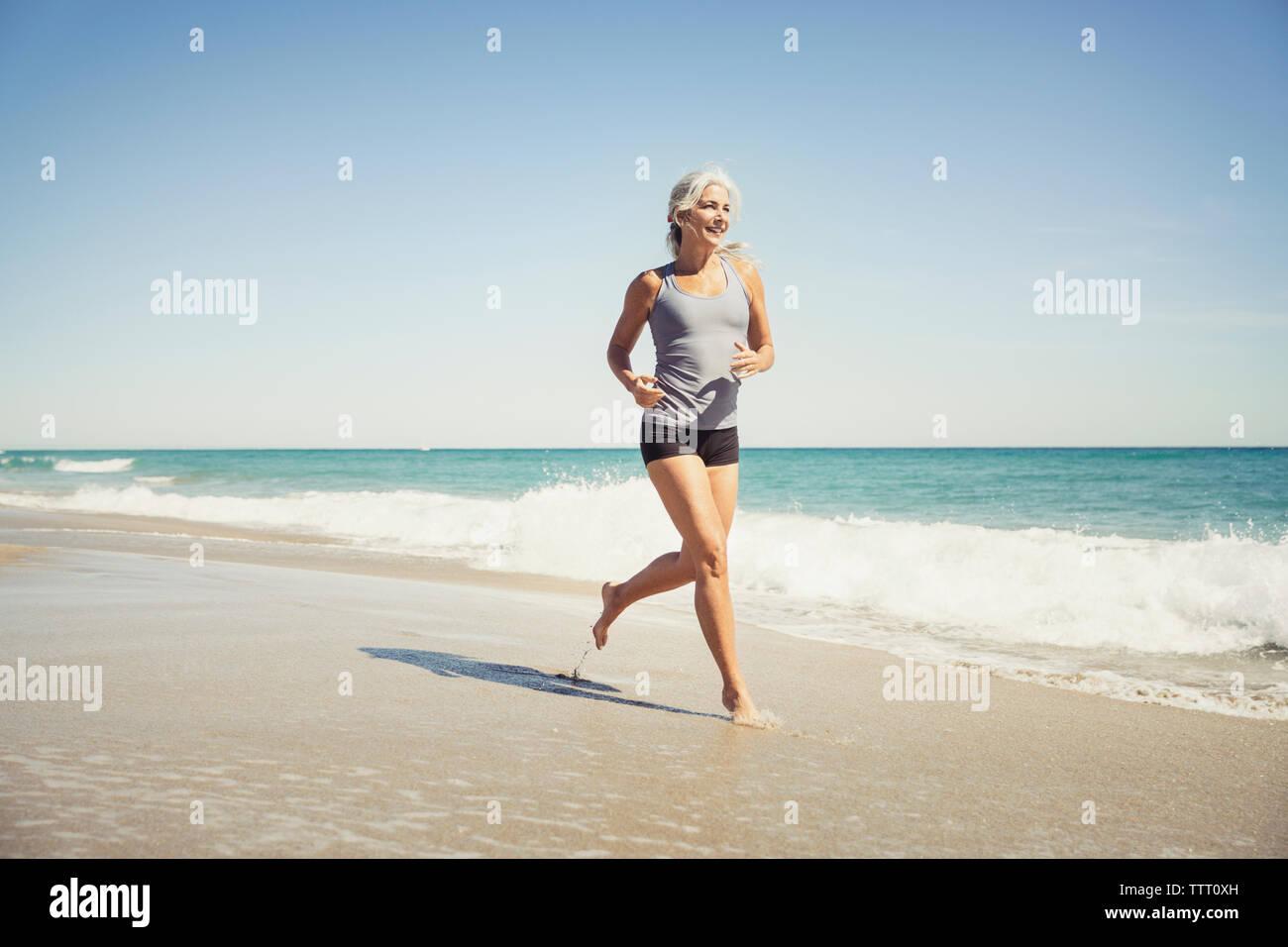 La longitud completa de la mujer madura, trotar en la orilla del mar en Delray Beach Imagen De Stock