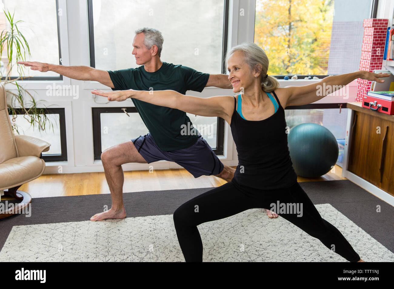 Pareja con los brazos extendidos y piernas separadas ejercicio en el hogar Imagen De Stock