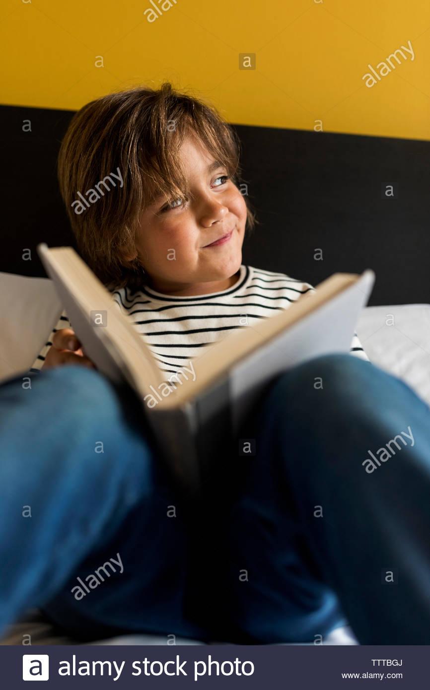 Joven en un dormitorio amarillo leyendo un libro en la cama Foto de stock