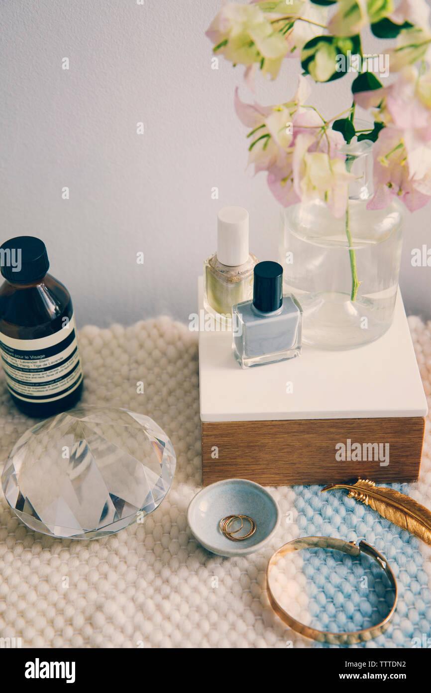Productos de belleza con joyas y cristal por florero en la mesa Foto de stock