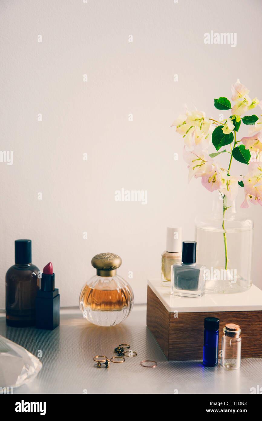 Productos de belleza con joyas y florero en la mesa contra la pared blanca Foto de stock