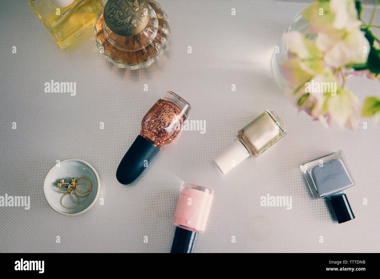 Un alto ángulo de visualización de productos de belleza con joyas de florero en la mesa Foto de stock