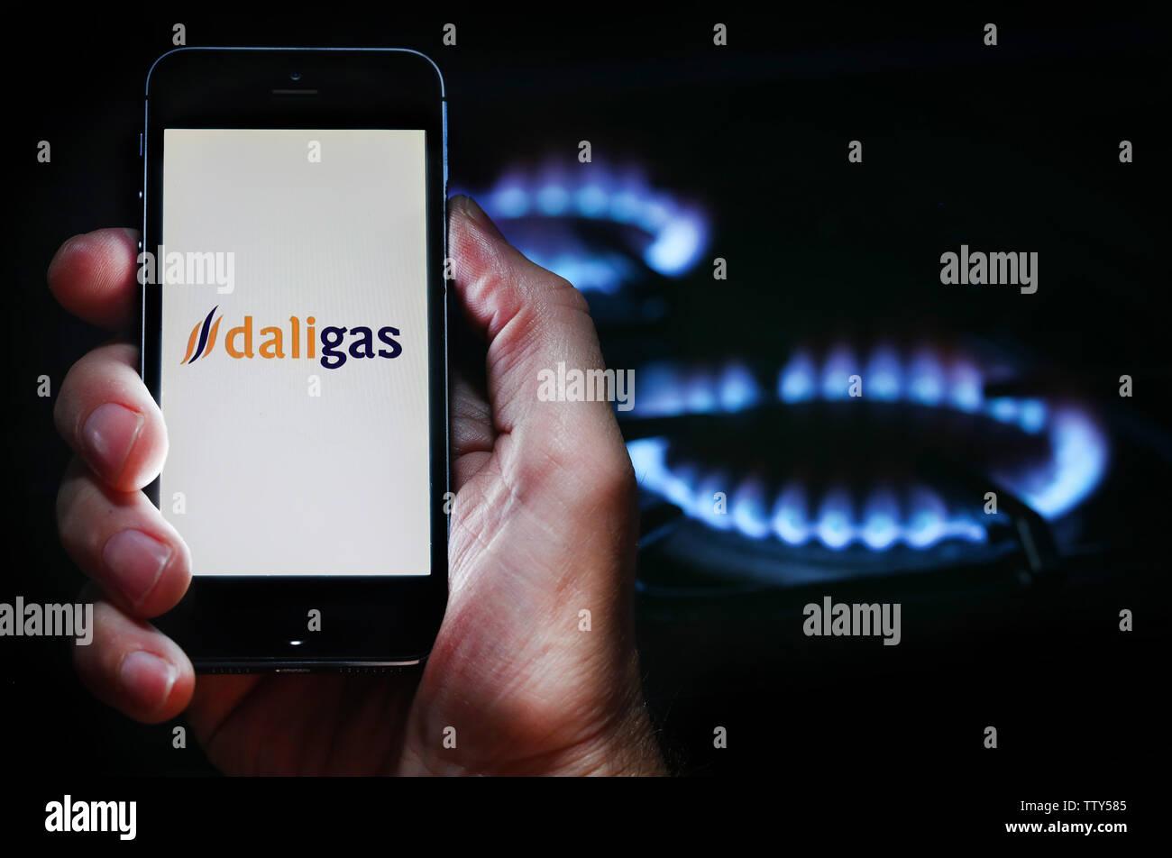 Un hombre mirando el logotipo del sitio web de la compañía de energía Daligas sobre su teléfono en frente de su cocina de gas (uso editorial solamente) Imagen De Stock