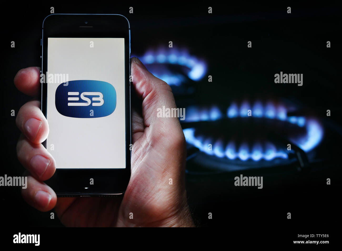 Un hombre mirando el logotipo del sitio web de la empresa energética ESB en su teléfono en frente de su cocina de gas (uso editorial solamente) Imagen De Stock