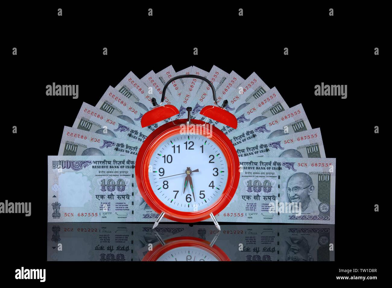 Reloj despertador con cien billetes de la rupia Foto de stock