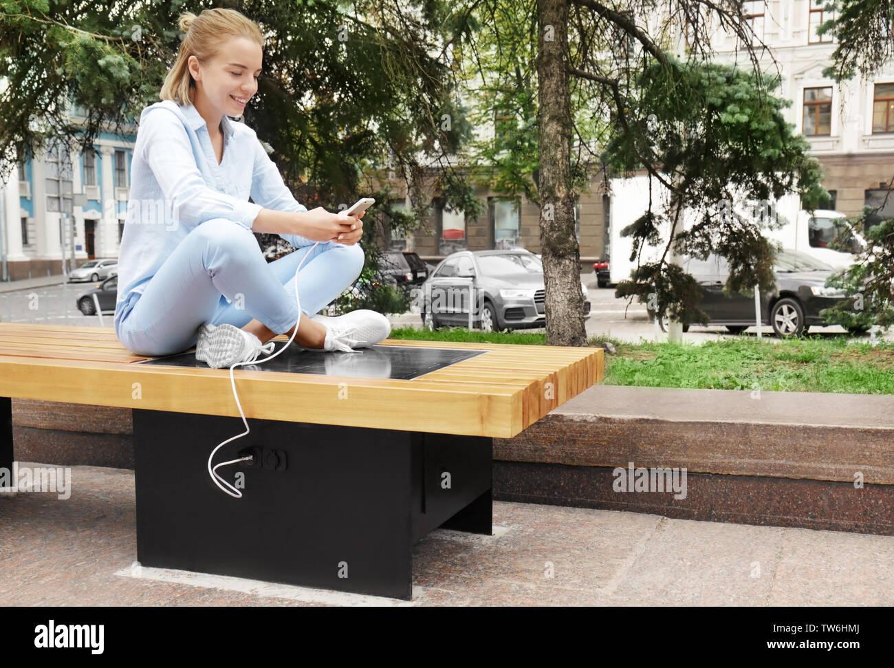 Mujer joven cargando el teléfono móvil en el banco de trabajo con panel solar Imagen De Stock