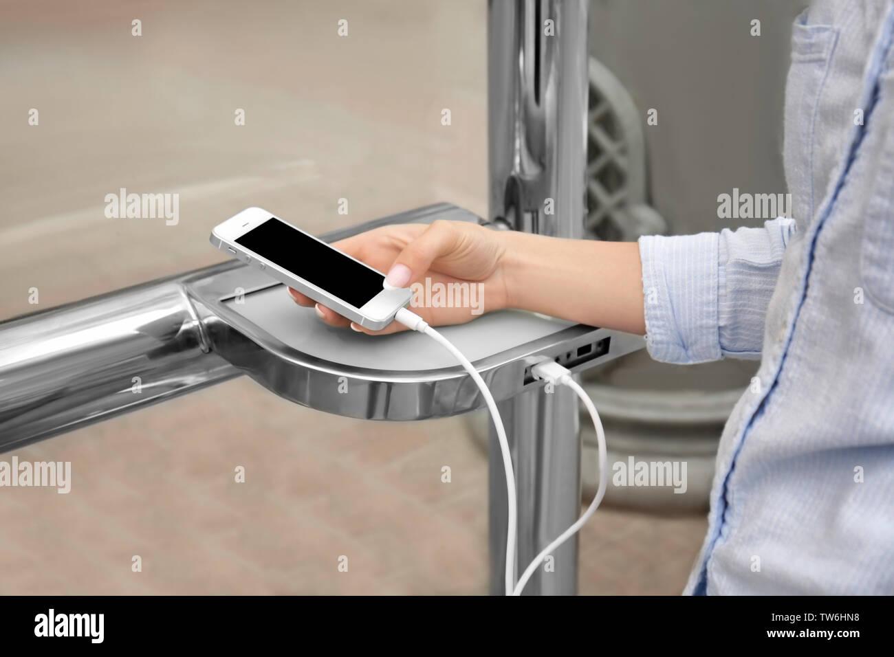 Mujer joven cargando el teléfono móvil al aire libre Imagen De Stock