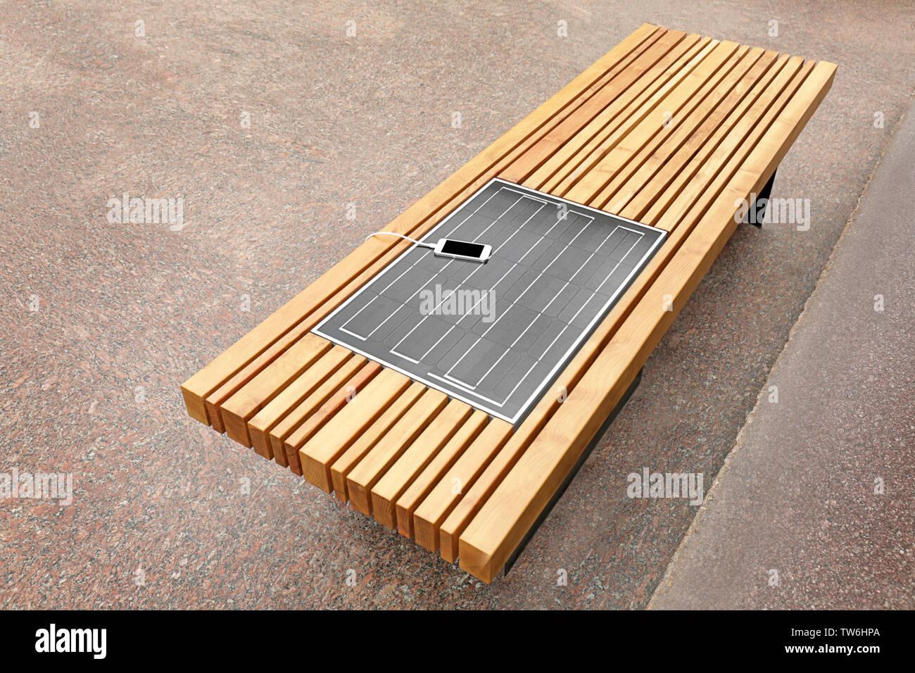 Teléfono móvil de carga en el banco de trabajo con panel solar Imagen De Stock