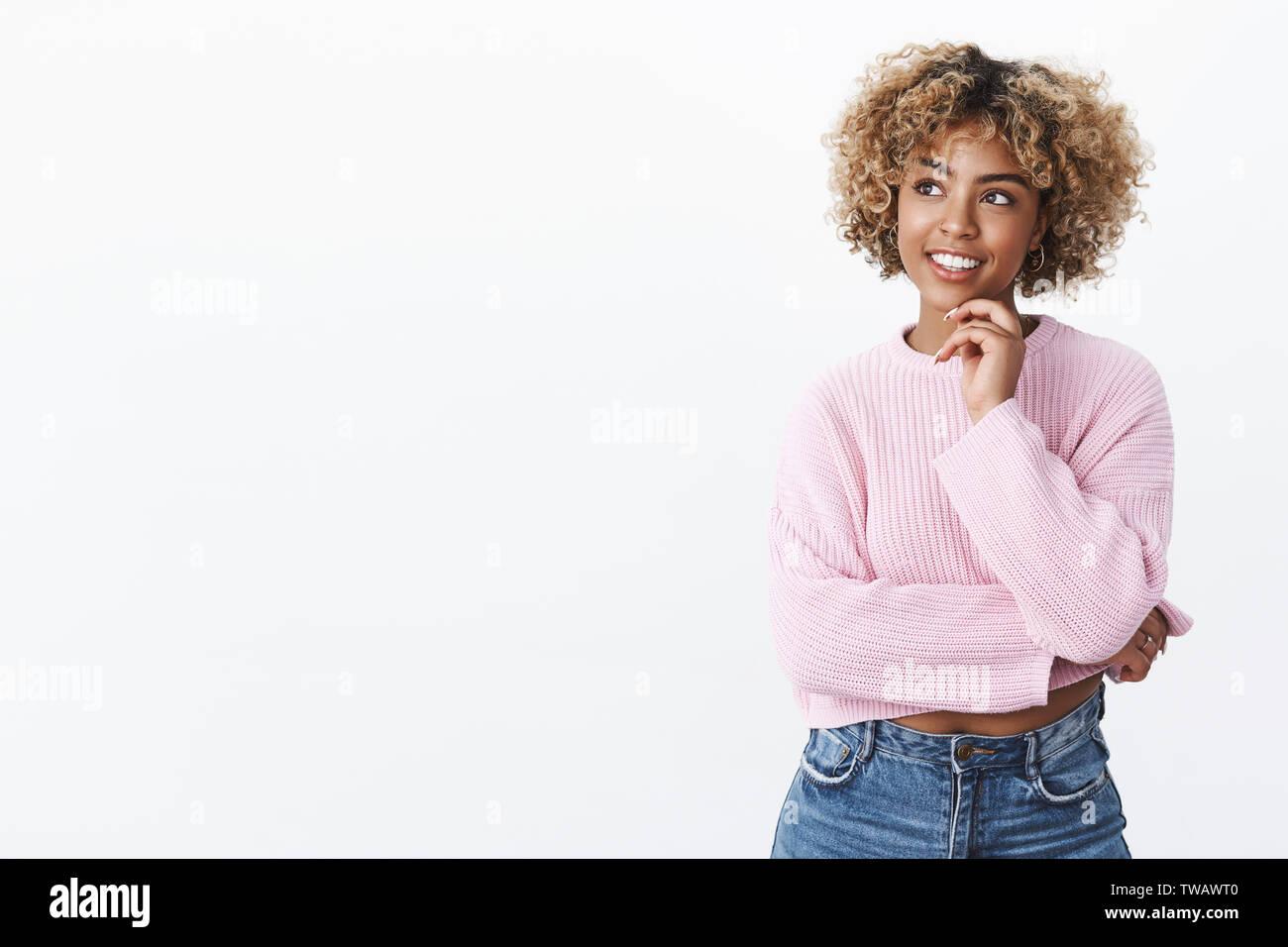 Atractiva joven estudiante afroamericana con cabello rubio sujetando con la mano en el mentón y mirando encantado en la esquina superior izquierda al pensamiento, posando Foto de stock
