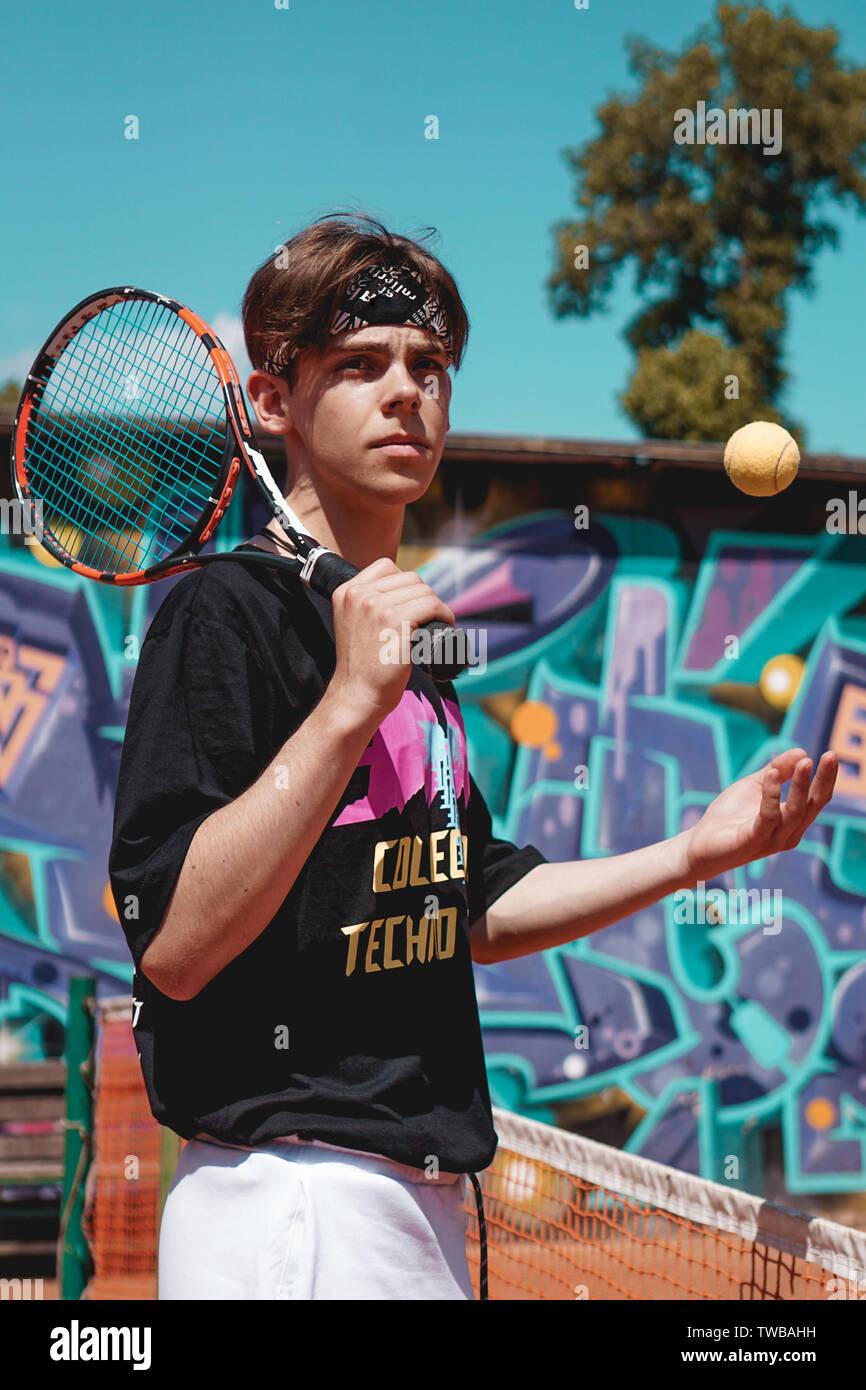 El deporte del tenis. Hombre jugando al tenis al aire libre. Retrato de joven atractivo en negro camiseta con raqueta Foto de stock