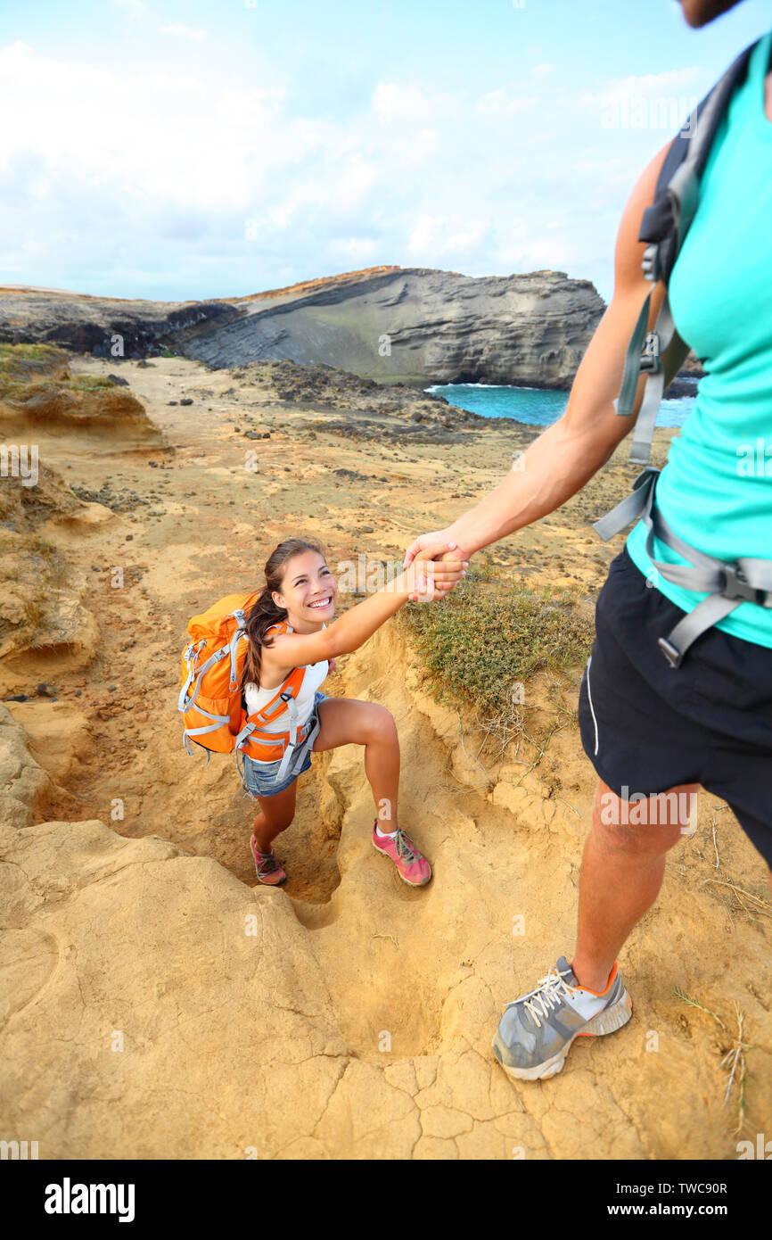 Ayuda - caminante mujer obtener mano de Senderismo Senderismo sonriendo feliz. Turistas mochileros caminando sobre arena verde Papakolea Beach, en Big Island, Hawaii, USA. Pareja joven viajar con mochilas. Foto de stock
