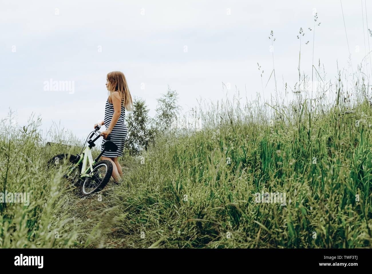 Chica en traje a rayas montando bicicleta. Pasar tiempo al aire libre. Niños jugando afuera en la primavera, el verano. Recuerdos de la infancia. Caminar en el parque, bosque. Ir de viaje, aventura en el desierto Foto de stock