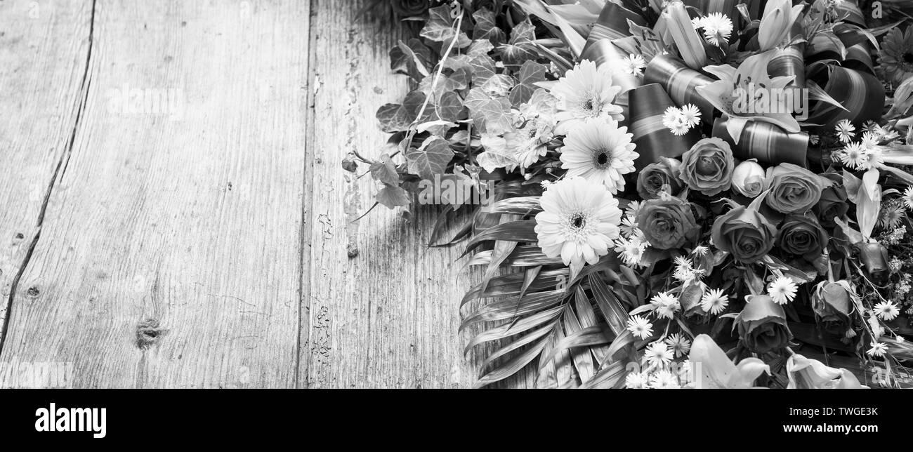 Ofrenda floral sobre fondo de madera desgastada con copia espacio en blanco y negro impresionante Imagen De Stock