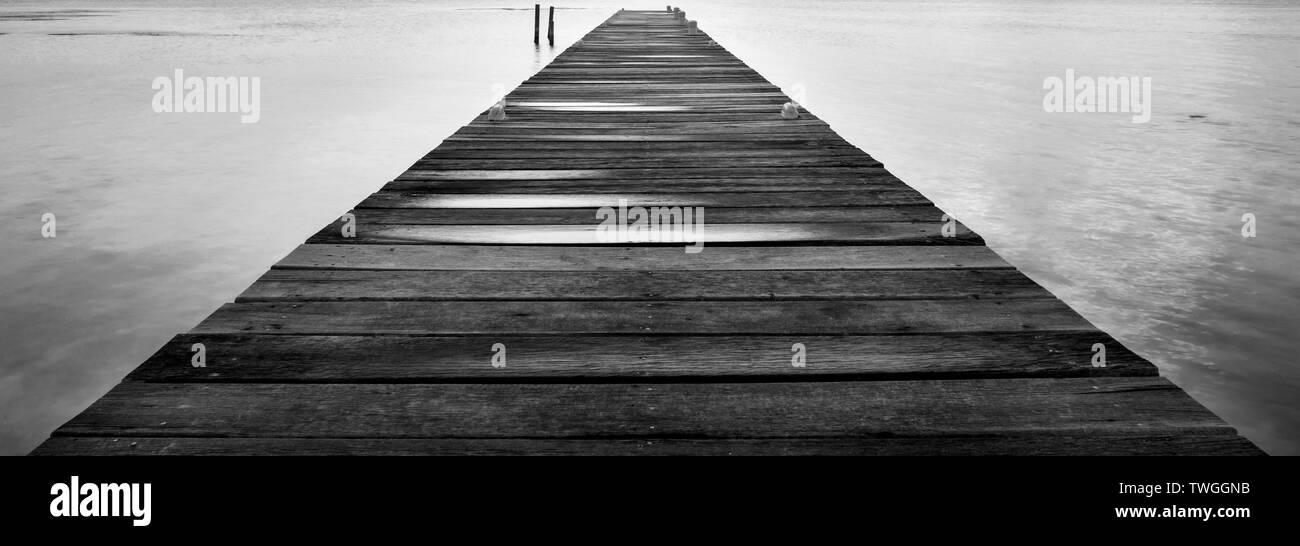 El amanecer de un embarcadero de madera alargándose hasta el océano silencioso en impresionante blanco y negro Imagen De Stock