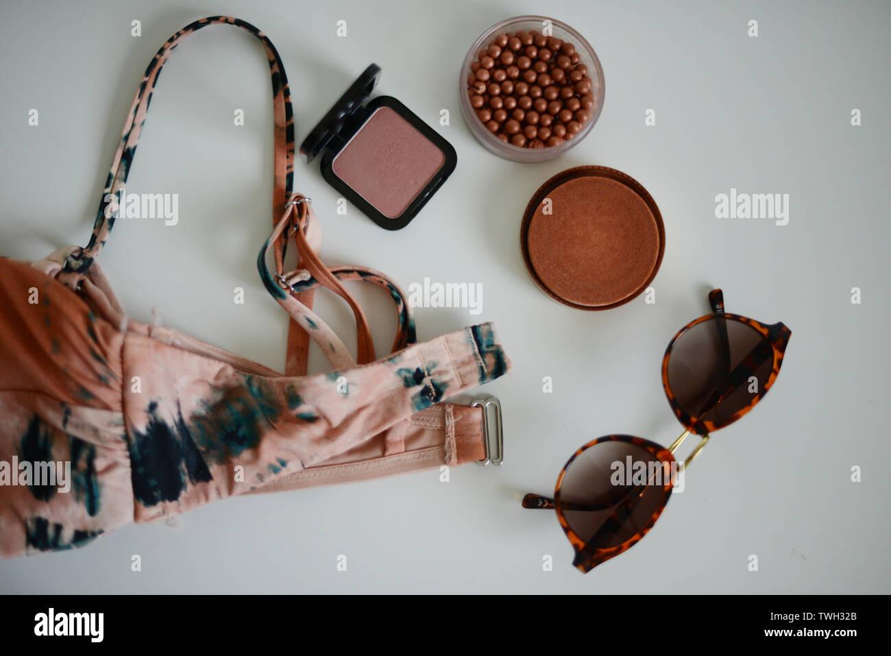 Bikini, sunglases y algunos productos de maquillaje en una tabla blanca Foto de stock