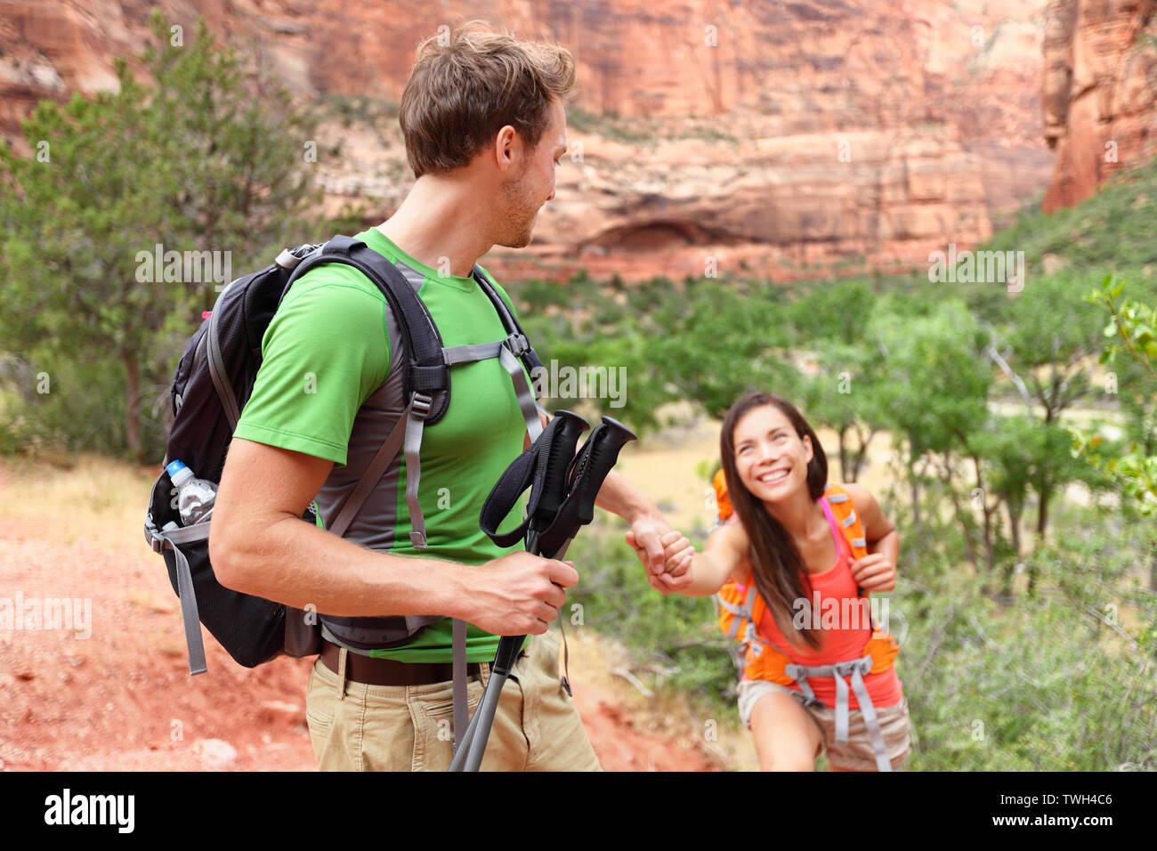 Mano - senderismo mujer obtener ayuda sobre caminata sonriendo feliz. Un estilo de vida activo excursionista pareja que viajaba. Hermosa raza mixta sonriente caucásico Asiático Femenino en el Parque Nacional de Zion, Utah, EE.UU.. Foto de stock