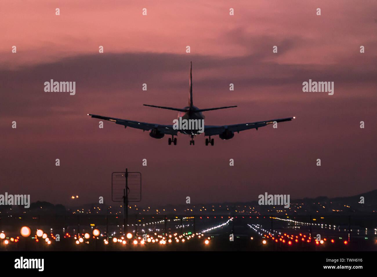 Los aviones de pasajeros de aterrizar en el Aeropuerto Internacional de Ciudad del Cabo al anochecer con la pista de aterrizaje claramente iluminado. Foto de stock