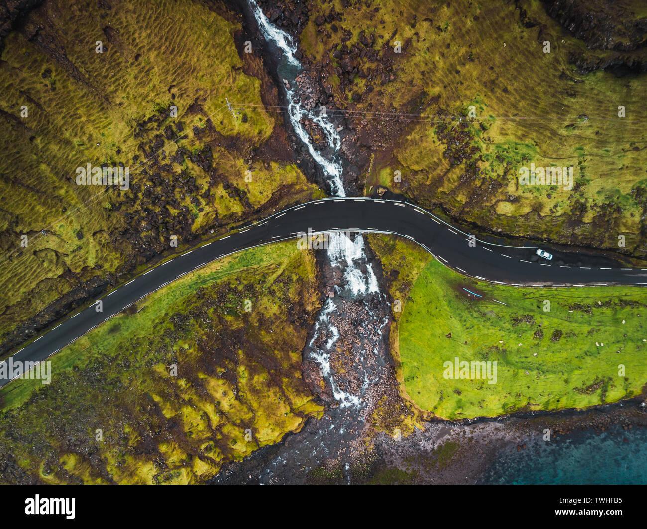 Imágenes aéreas de la Fosa de cascada desde arriba durante principios de la primavera con cumbres nevadas y verdes tonos (Islas Feroe, Dinamarca) Foto de stock