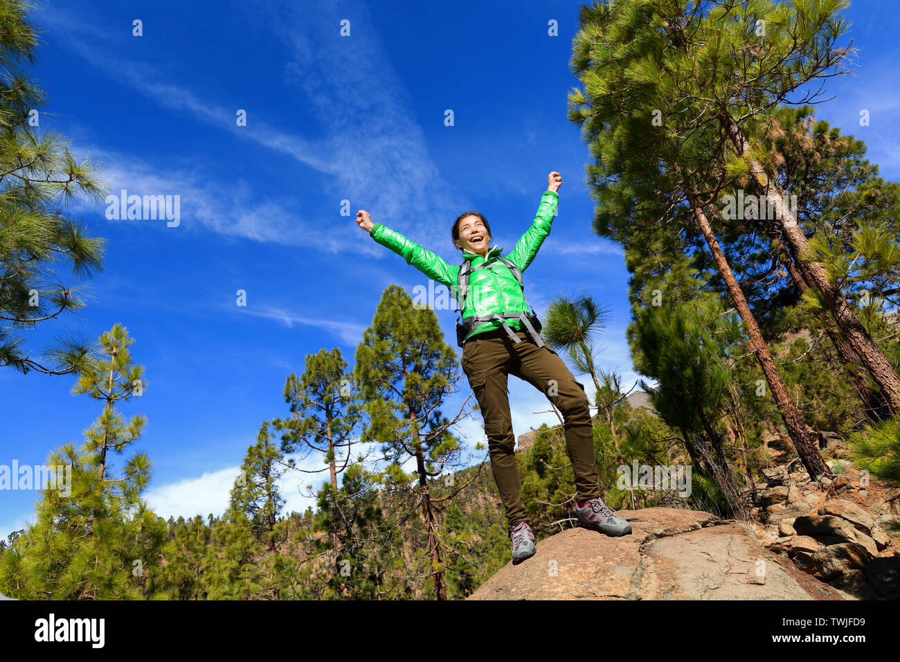 Senderismo mujer alcanzando cumbre aclamando superior celebrando en la cima de la montaña con brazos extendidos hacia el cielo. Feliz excursionista hembra. Foto de stock