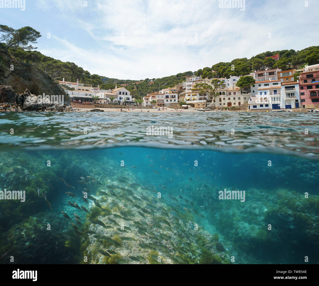 España pueblo costero con playa y peces bajo el agua, el mar Mediterráneo, Cala Sa Tuna, Begur, Costa Brava, Cataluña, vista dividida sobre y bajo el agua Foto de stock