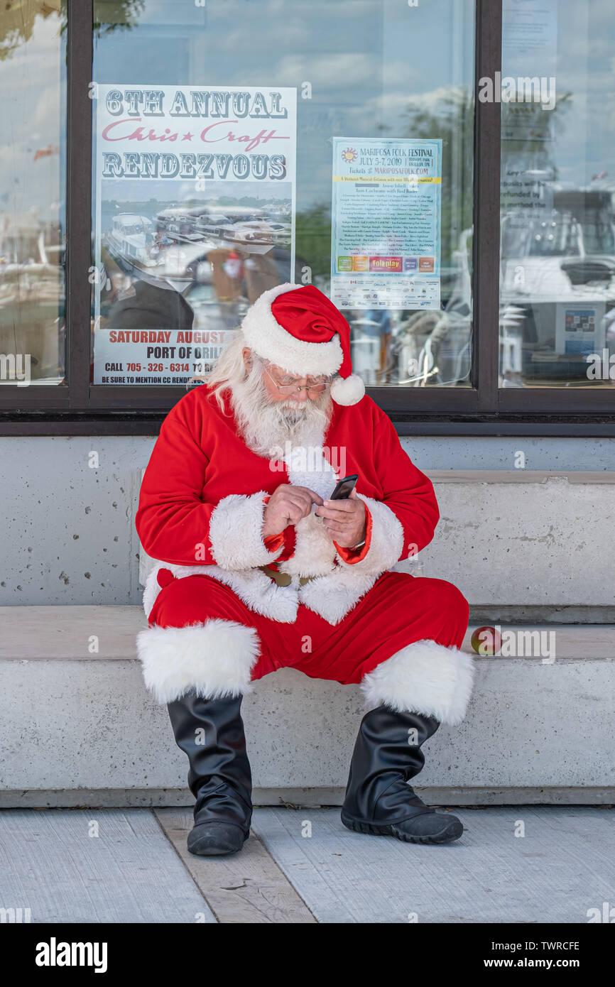 Santa Clause controlar su teléfono durante un descanso en la celebración anual de la Navidad en junio en Orillia Ontario Canada. Comprobación nughty bonita lista. Foto de stock