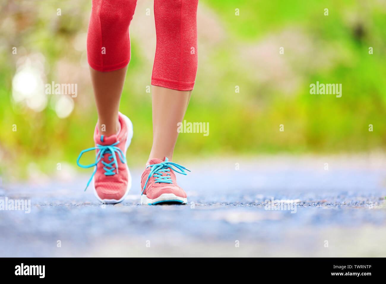 Trotar mujer con piernas atléticas y zapatos para correr. Mujeres caminando por senderos de bosque en concepto de estilo de vida saludable con hasta cerrar en zapatos para correr. La atleta femenina formación emparejador afuera. Foto de stock