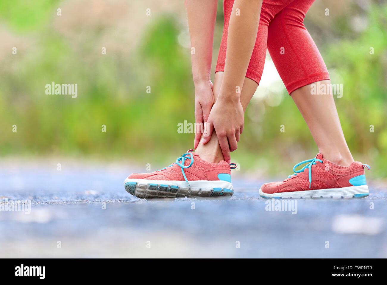 Rotura de tobillo torcido - ejecución de lesiones deportivas. Corredoras, tocar de pies en el dolor debido a esguince de tobillo. Foto de stock