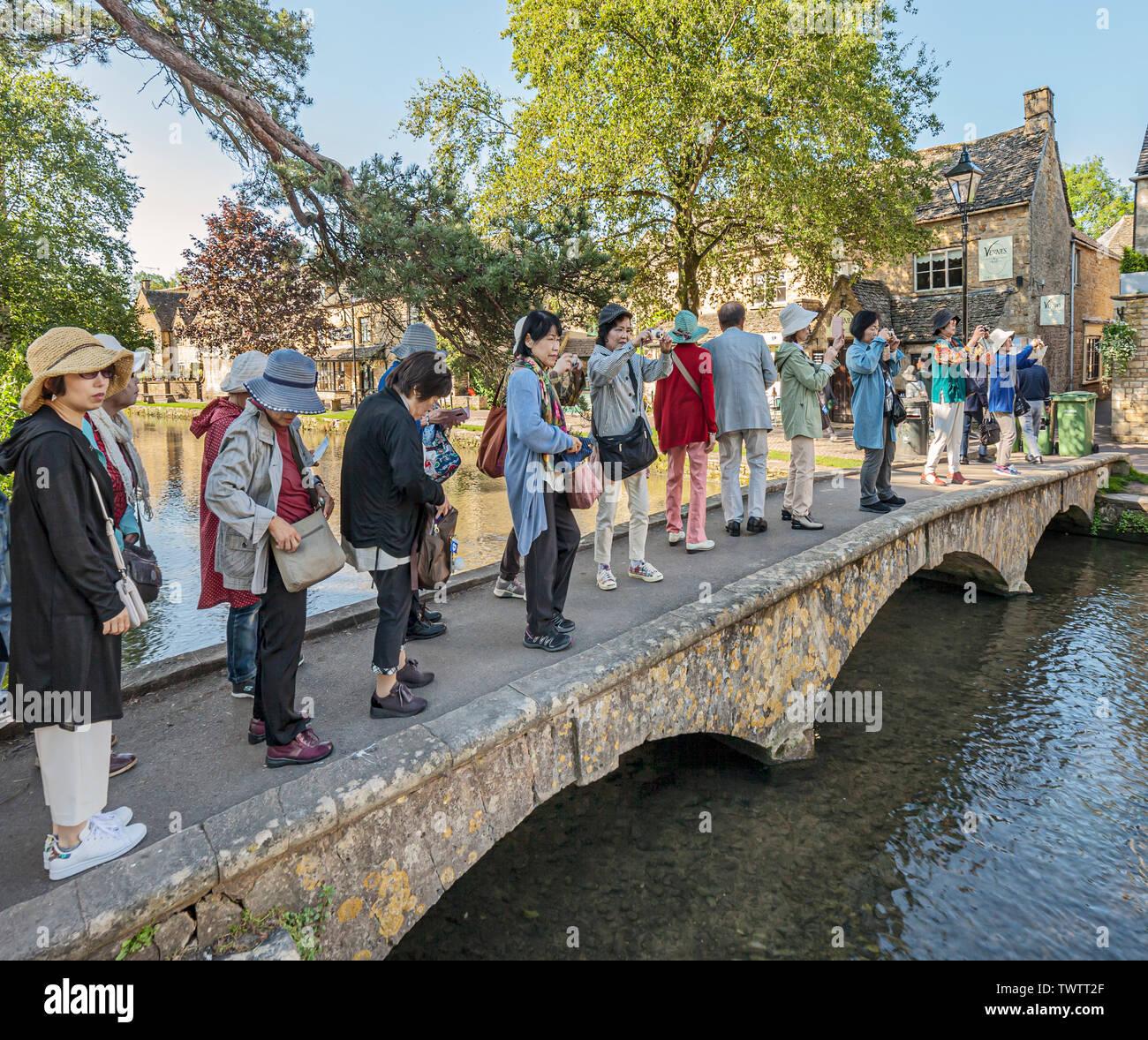 Grupo de turistas visitando Bourton sobre el agua. Foto de stock