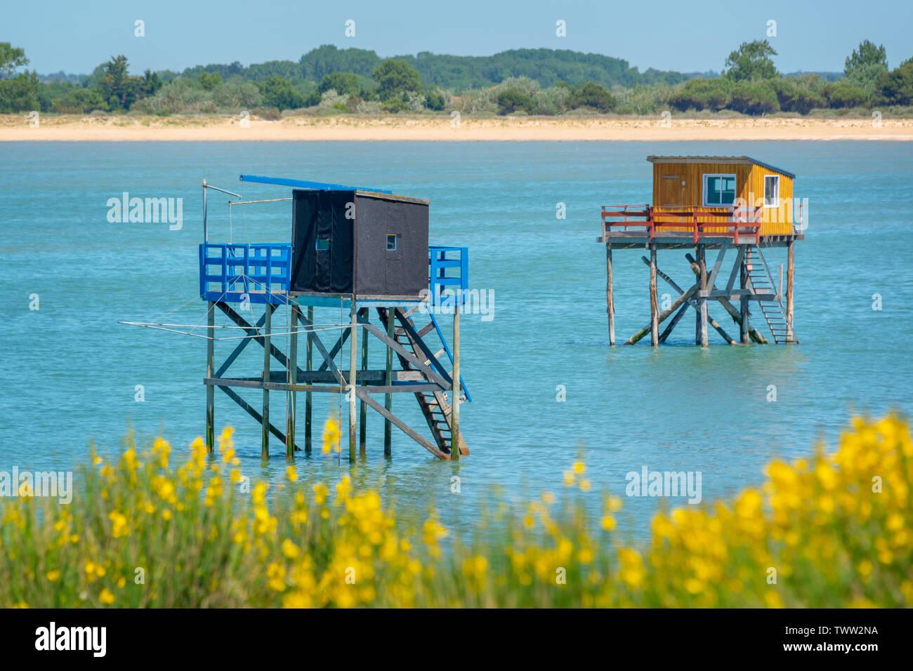 Típicas y coloridas cabañas de pesca de madera sobre pilotes en el Océano Atlántico cerca de La Rochelle, Francia Foto de stock